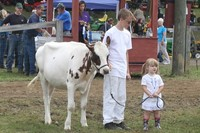 Two children standing next to a cow