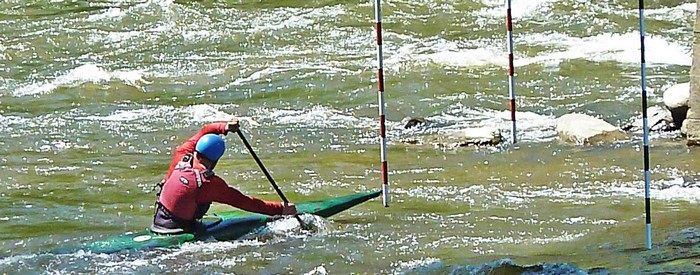 Kayak with man rowing upstream between the poles